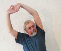 John Hughes demonstrating the overhead stretch for cyclists